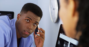 African American doctor talking to colleague. Close up of African American doctor talking to female colleague while using smartphone Royalty Free Stock Images