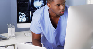 African American doctor working at computer and laptop stock photography