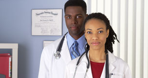 African American doctors standing in hospital office. Close up of African American doctors in hospital office looking at camera royalty free stock photography
