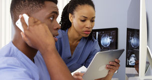 African American doctors using tablet and phone to work together. Two African American doctors using tablet and phone to work together Royalty Free Stock Images