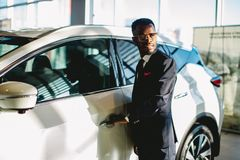 African american driver opening his new car door royalty free stock photos