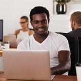 African American entrepreneur in a tech startup office. Young African American entrepreneur working on a laptop in a tech startup office Royalty Free Stock Photo