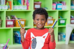 African American ethnicity kid holding group of color pencil smi. Ling at library in kindergarten preschool classroom.education concept Stock Image