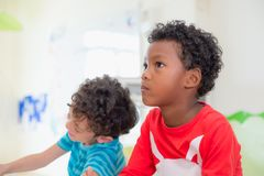 African American ethnicity kid with moody emotion sitting in cla. Ssroom in kindergarten ,education concept Stock Photo
