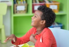 African American ethnicity kid smiling at library in kindergarten preschool classroom.happy emotion.education concept.  royalty free stock images