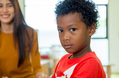 African American ethnicity kid with teacher smiling at background in kindergarten classroom stock photography