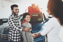 African american family at car dealership. Father, mother and son near new car. Man is giving keys to woman. African american family at car dealership. Father Stock Image