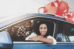 African american family at car dealership. Mother and father are sitting in new car with ribbon on top. stock images