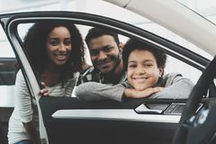 African american family at car dealership. Mother, father and son are pising in window of new car. stock photo