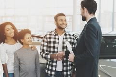 African american family at car dealership. Salesman and man shaking hands, congratulating with new car. stock photography