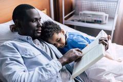 African american family in clinic. Side view of african american father reading book to son in clinic Stock Photos