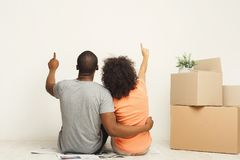Black couple looking up, sitting on floor. African-american family couple looking up, sitting on floor in new apartment with moving boxes, dreaming about future Stock Photos