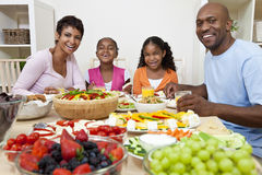 African American Family Eating At Dining Table. An attractive happy African American, smiling family of mother, father, two daughters eating salad and healthy Stock Images