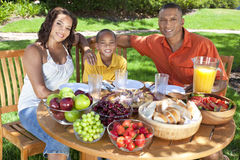 African American Family Eating Food Outside. A happy, smiling African American family, mother father & son eating healthy food at a table outside, the father is Royalty Free Stock Images