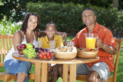 African American Family Eating Food Outside. A happy, smiling African American family, mother father & son eating healthy food at a table outside, the father is Stock Image