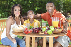 African American Family Healthy Eating Outside. An attractive happy, smiling African American family of mother, father, son, men women, boy child eating healthy Stock Photo