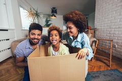 African American family, parents and daughter, unpacking boxes and moving into a new home royalty free stock photos