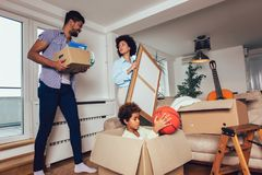 African American family, parents and daughter, unpacking boxes and moving into a new home royalty free stock photography