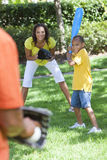 African American Family Playing Baseball. African American family, man, woman, boy child, mother, father, son playing baseball together outside Stock Photo