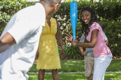 African American Family Playing Baseball. African American family, man, woman, girl and boy children, mother, father, son & daughter playing baseball together Stock Photo
