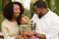 Happy African American family with their baby. stock images