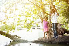 African American family pointing up the sky and standing on tree around the lake. Royalty Free Stock Photos