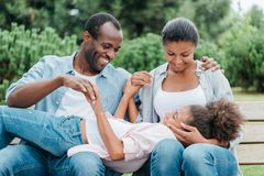 African american family resting on bench. Cheerful african american family resting on bench while spending time together in park royalty free stock image