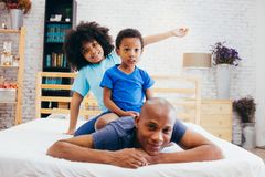 African American family of three, kids sitting on father`s back at home stock images
