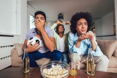 African American family of three watching tv and cheering sport games on sofa at home stock photos