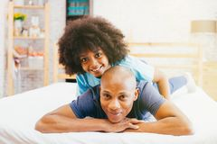 African American family of two, child sitting on father`s back at home. stock photography