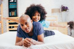 African American family of two, child sitting on father`s back a royalty free stock photo