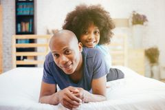 African American family of two, child sitting on father`s back at home royalty free stock image