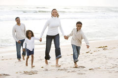 African-American family walking on beach. Happy African-American family with two children holding hands and walking on beach Stock Images