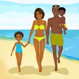 African american family walking happy along beach Stock Photo