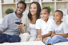 African American Family Watching Television. African American family, mother & father parents and two sons, having fun watching television together using the Stock Photo