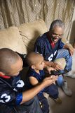 African-American family watching tv with boy holding remote. royalty free stock images