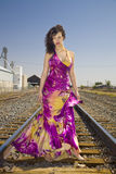 African American Fashion Model on Railroad Tracks. Attractive African American fashion model in a gown photographed on railroad tracks in an urban industrial royalty free stock photography