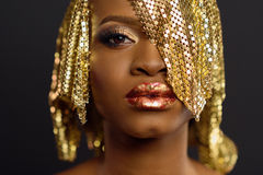 African-american fashion style. Beautiful woman wearing golden headdress looking at camera while standing against black background Stock Image