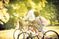 New day for school and work. African American father and daughter driving bike trough park stock photography