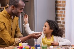Father and daughter having fun and painting faces, easter concept. African american father and daughter having fun and painting faces, easter concept Royalty Free Stock Images