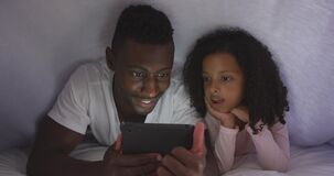 African american father and daughter looking at phone in bed