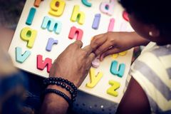 Learning Alphabet. African American father and daughter in nature. Learning Alphabet. Close up. Focus is on hands royalty free stock photo