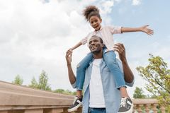 African american father and daughter in park. Low angle view of smiling african american father and daughter piggybacking together in park Stock Photography