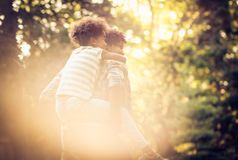 Kid on father piggyback. African American father and daughter playing in park. Carrying on piggyback. From back royalty free stock photo