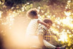 Kid on father piggyback. African American father and daughter playing in park. Carrying on piggyback royalty free stock photo