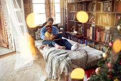 African American father and daughter reading fairy tales for the royalty free stock images