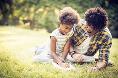 Learning for school. African American father and daughter writing together in nature royalty free stock photos