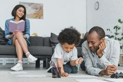 African american father drawing with son and mother reading book. At home royalty free stock photo