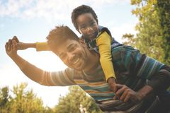 African American father enjoying in autumn day with daughter. stock image