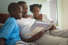 African American father with his children reading a storybook on bed in bedroom royalty free stock images
